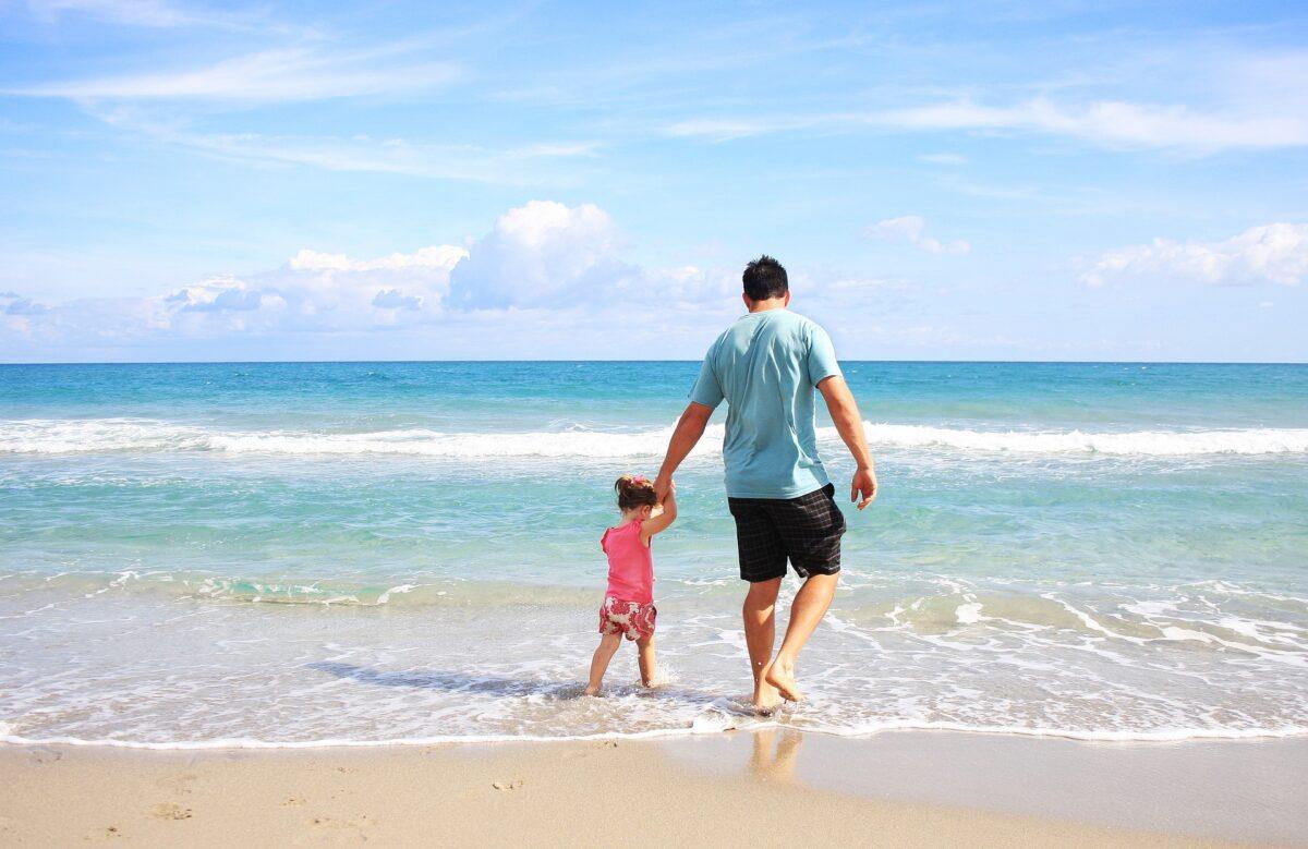 海で波と戯れる父と子