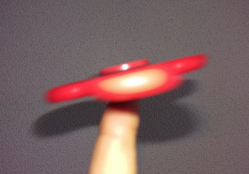 ハンドスピナーを指の上でまわしている