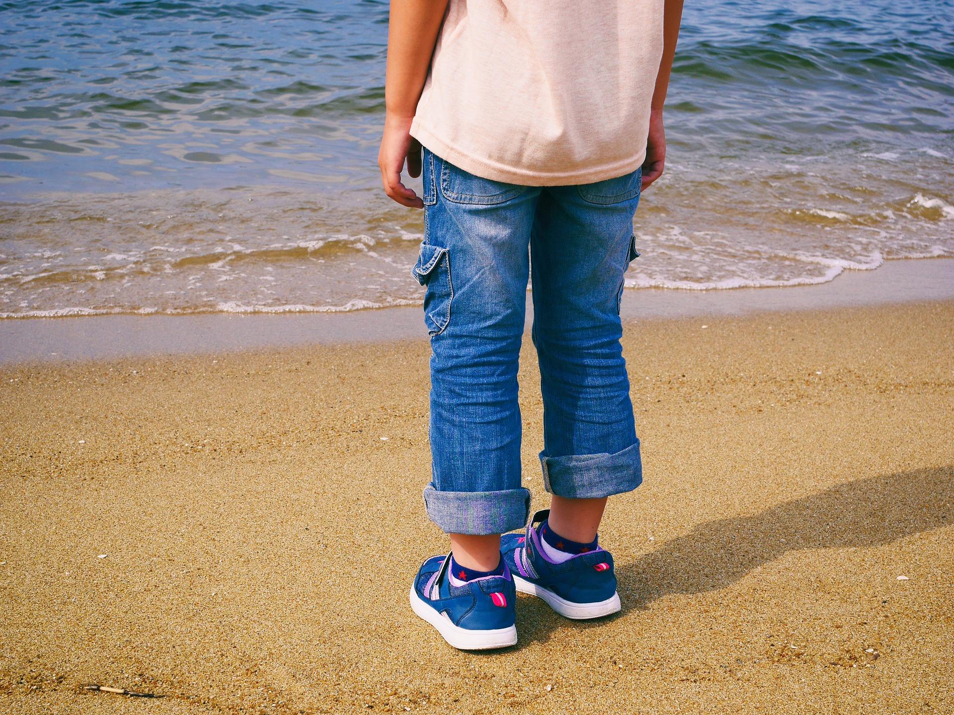 海を前に砂浜に立つ男の子の後ろ姿