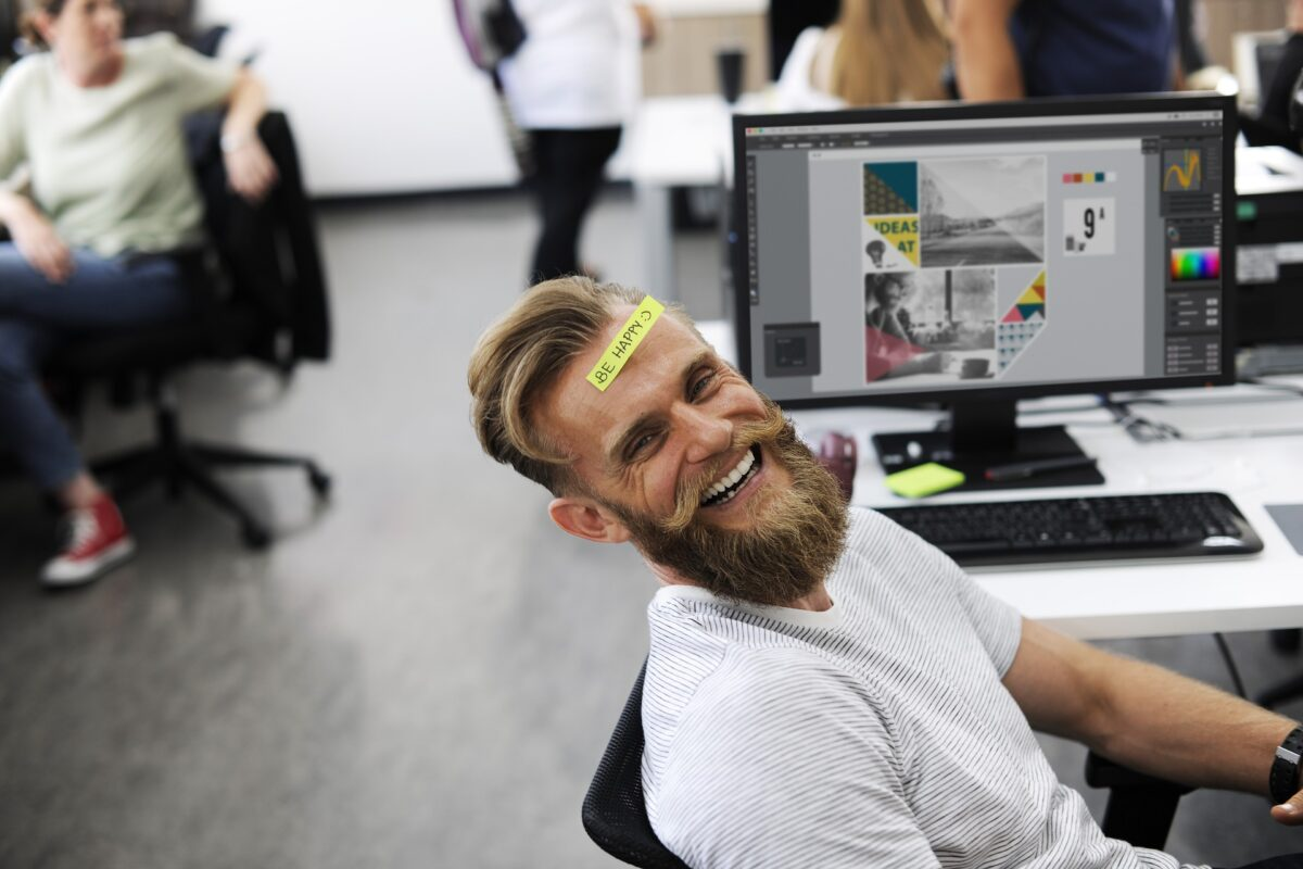 職場のデスクで笑う男性の画像