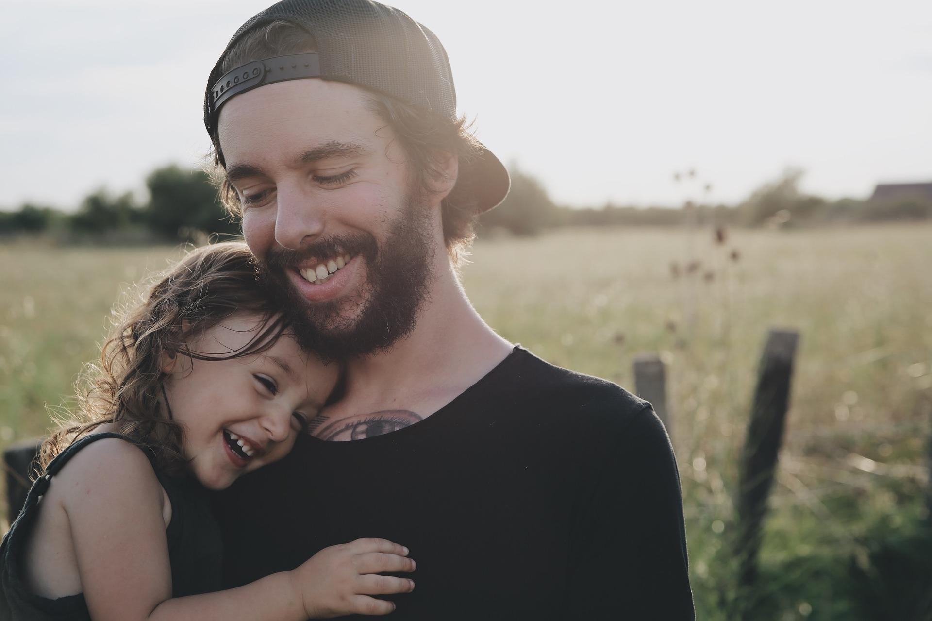 笑顔でハグする父と娘の画像
