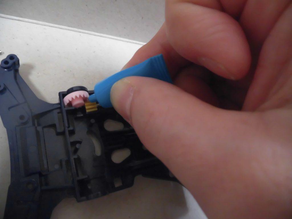 ミニ四駆のシャーシにギヤを設置し、グリス注入している場面の画像