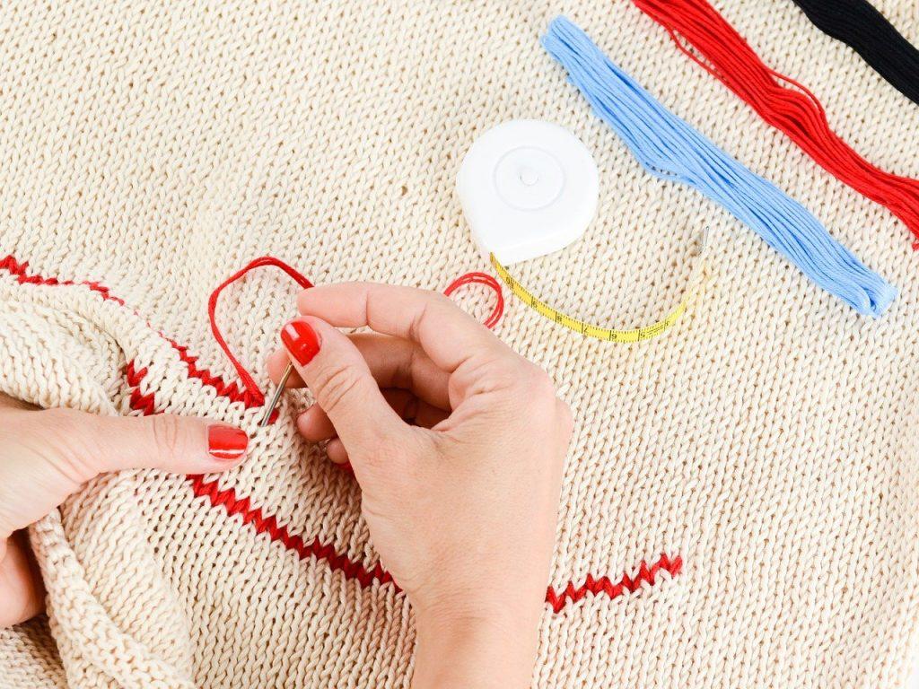 刺繍の糸と、刺繍をする人の手の画像