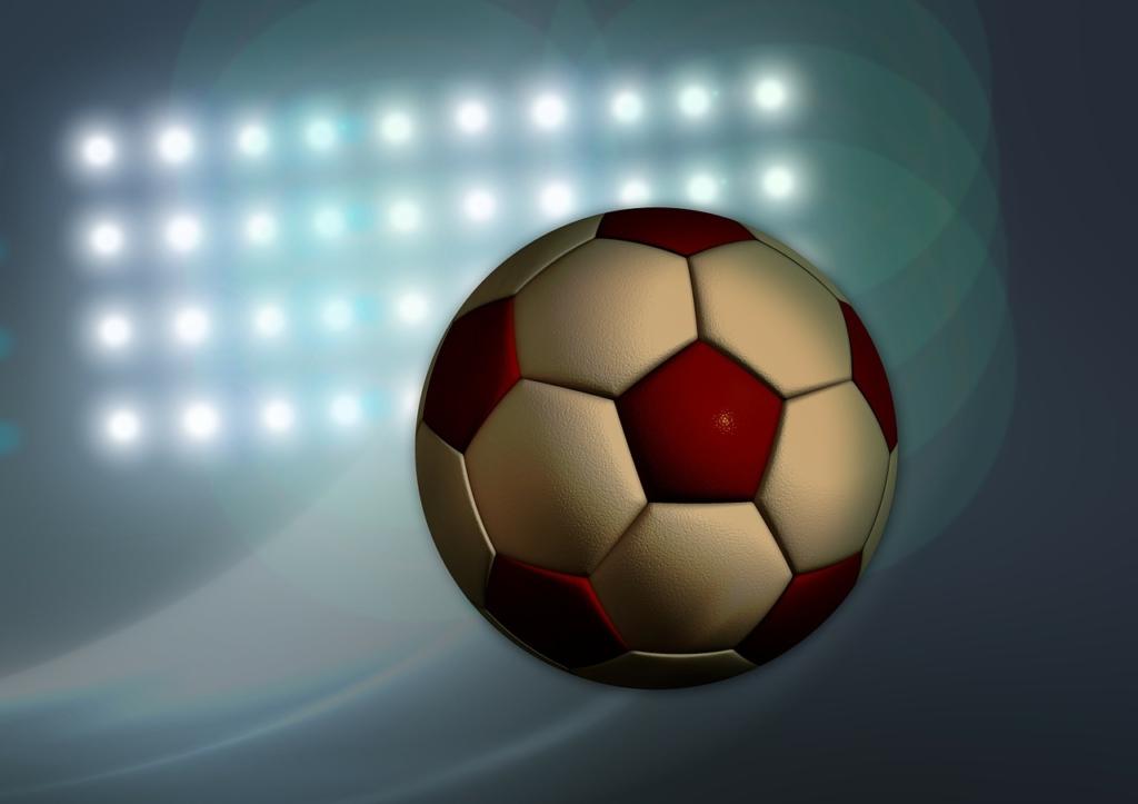 スタジアムの照明とサッカーボール
